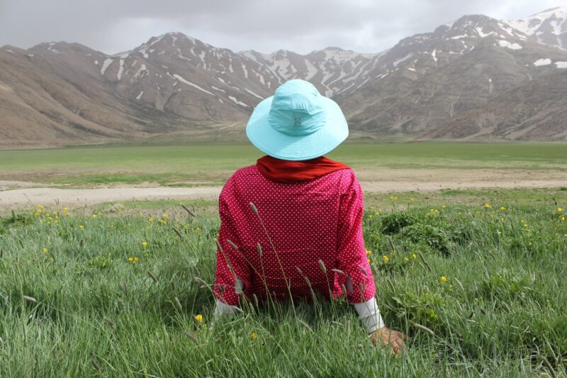 Person sitting on grass field looking at mountains