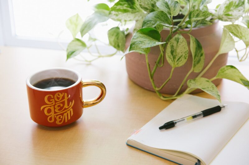 A desk with a plant, coffee, and a notebook
