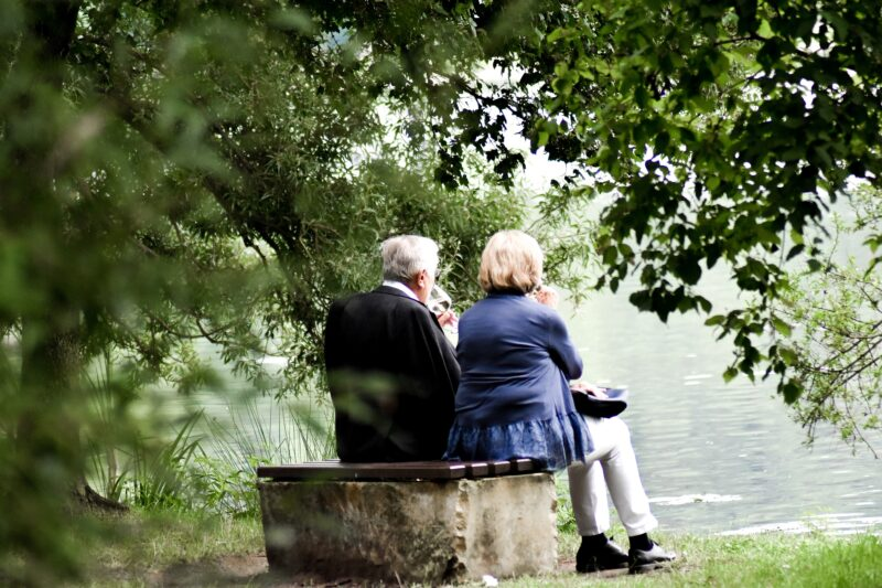 Older couple sitting by nature